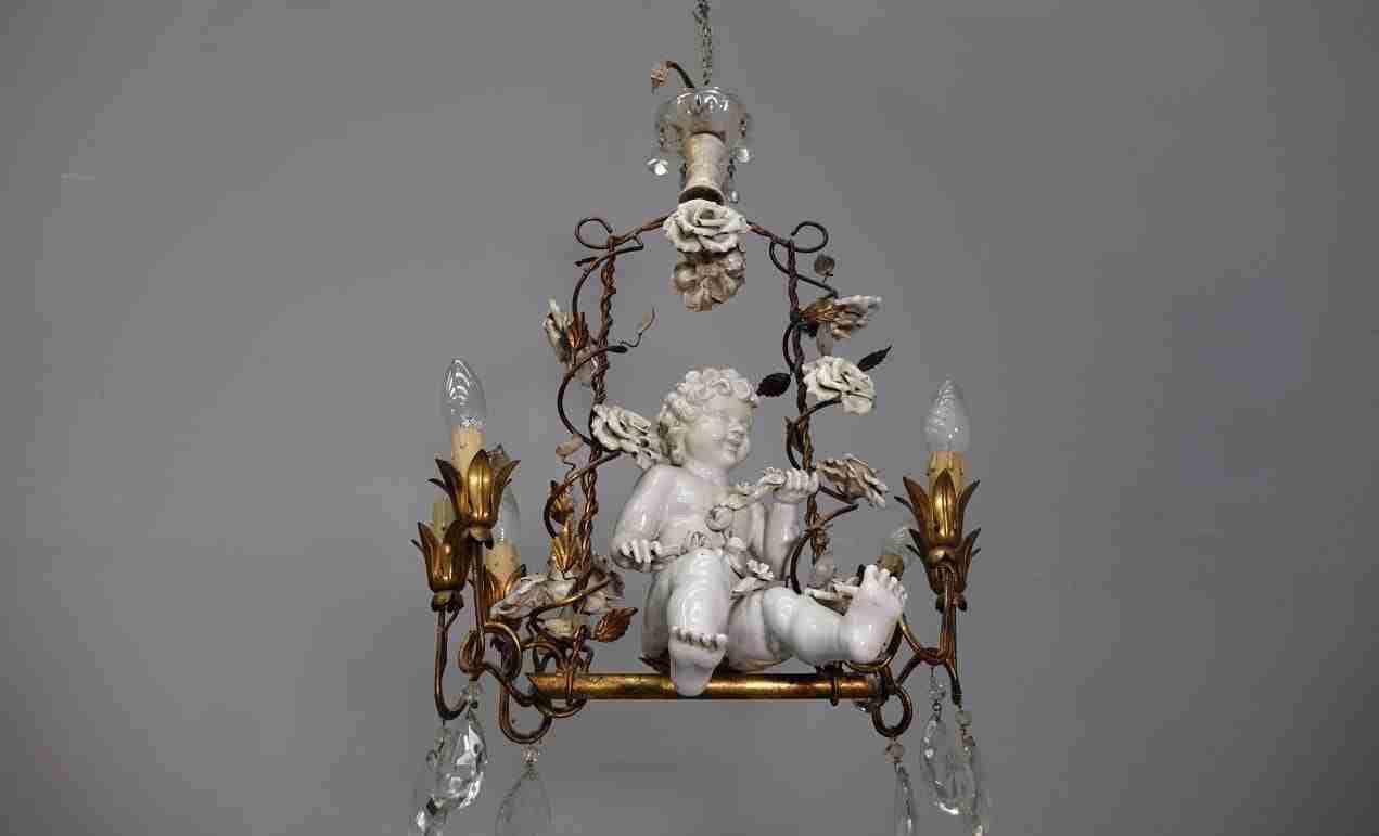 lampadario con putto in ceramica sull'altalena