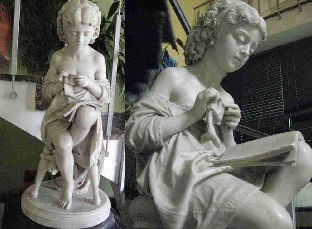 scultura in marmo ragazza che cuce