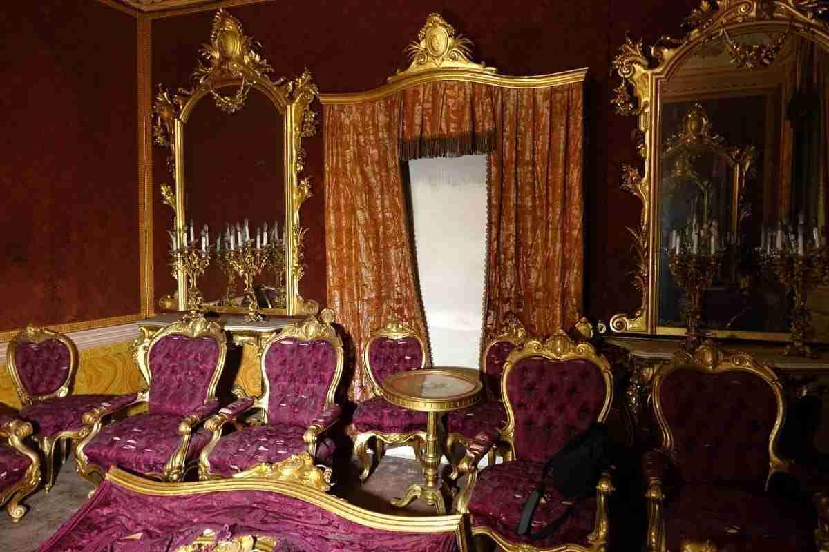 Salotto dorato specchiere console mantovane poltrone divani